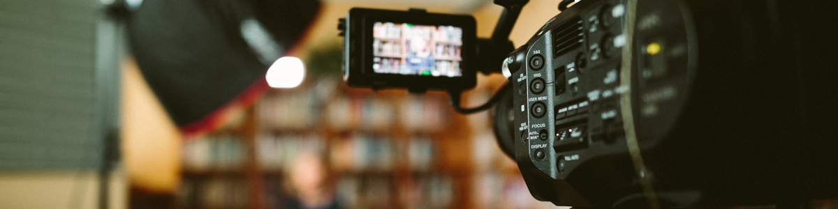 Woman being filmed in a library. Photo by Sam McGhee on Unsplash