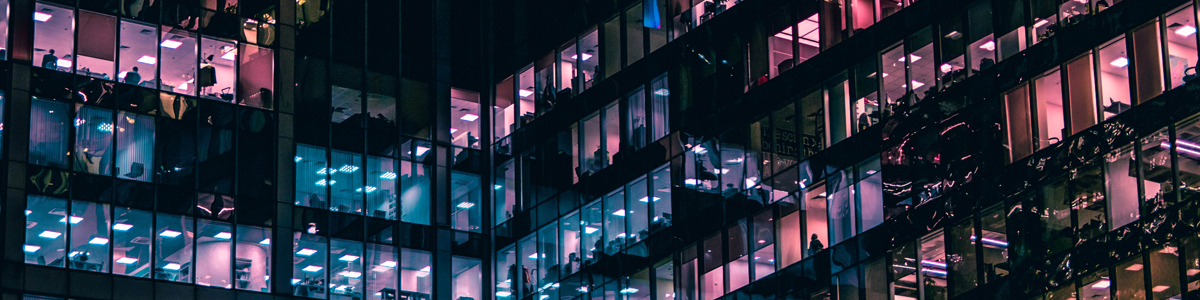 Windows in a tall building lit at night. Photo by Mike Kononov on Unsplash
